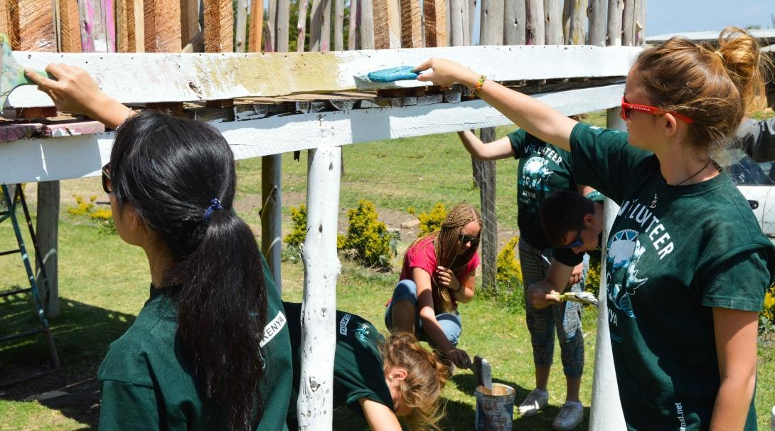 Volunteers paint a jungle gym in Kenya while volunteering abroad under 18.